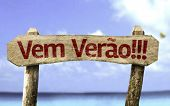 Summer Coming!!! (In Portuguese) wooden sign with a beach on background