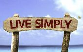 Live Simply wooden sign with a beach on background