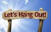 Let's Hang Out! wooden sign on a summer day