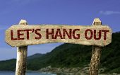 Let's Hang Out wooden sign with a beach on background