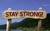 Stay Strong wooden sign with a beach on background