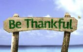 Be Thankful sign with a beach on background