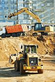 wheel loader and excavator machine loading dumper truck at construction area sand quarry