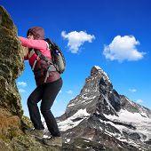 Girl on rock, in the background mount Matterhorn - Swiss Alps, Europe