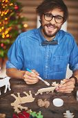 Happy young man preparing wooden shape of deers for Christmas