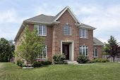 Brick suburban home with arched window above entry