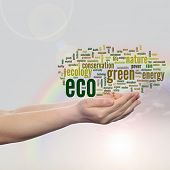 Concept or conceptual abstract green ecology, conservation word cloud text man hand, rainbow sky background for environment, recycle, earth, clean, alternative, protection, energy, eco friendly or bio