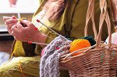 basket with balls of yarn  and woman knitting