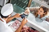 High angle view of female customer paying through smartphone at butchery