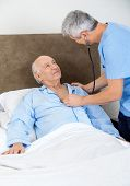Male caretaker checking senior man with stethoscope in bedroom at nursing home
