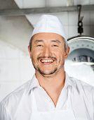 Portrait of cheerful mature male butcher in butchery