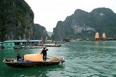 Fishing boat and tourist argosy in Halong Bay.