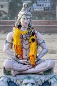 RISHIKESH, INDIA - NOVEMBER 13, 2012: Servants decorate large statue of Hindu Lord Shiva with flowers for the Ganga Aarti ceremony on November 13, 2012 in Rishikesh, India.