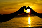 young loving couple on wedding day on tropical beach and sunset sea background, heart shaped figure made by hands