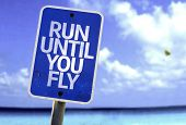 Run Until You Fly sign with a beach on background