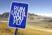 Run Until You Fly sign with a desert background