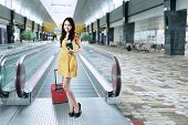 pic of carry-on luggage  - Portrait of young asian girl standing in airport corridor while carrying luggage and holding passport - JPG