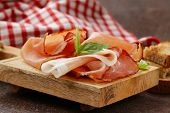 smoked ham jamon (Parma) with basil leaves on a wooden board