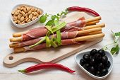 stock photo of oregano  - Grissini bread sticks with ham olives fresh oregano herbs and peanuts - JPG