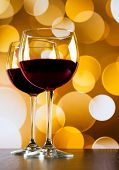 Red Wine Glasses On Wood Table Against Golden Bokeh Lights Background