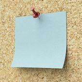 Blank blue sticky note pinned on a cork board