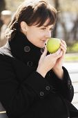 Woman In Black Smelling Apple