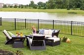 image of ponds  - Cute little blond girl standing amongst comfortable modern design garden furniture with armchairs and tables arranged on a neat green lawn overlooking a tranquil pond and wrought iron railing - JPG