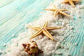 pic of sea life  - Sea stars on sea salt on wooden background - JPG