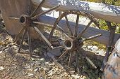 stock photo of wagon wheel  - Derelict old pioneer days wagon wheels propped up on a fence in a ranch in New Mexico - JPG