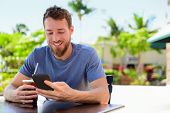 stock photo of sms  - Smartphone man sms texting drinking cold coffee drink at outdoor cafe on terrace in summer - JPG