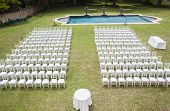 foto of lawn chair  - White chairs dozens positioned on grass lawn outdoors for private wedding occasion - JPG