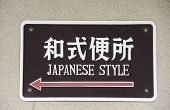 stock photo of defecate  - Sign in Japanese characters and English language to bathroom in Japanese style - JPG