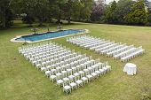 image of lawn chair  - White chairs dozens positioned on grass lawn outdoors for private wedding occasion - JPG