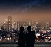 stock photo of city silhouette  - Silhouette of couple sit on ground point faraway on the roof above the city in the night - JPG