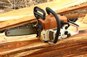 stock photo of chainsaw  - Gas powered chainsaw on the woods of recently cut down the tree - JPG