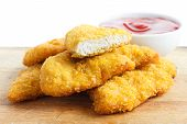 stock photo of fried chicken  - Golden fried chicken strips on wood board - JPG