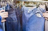 stock photo of thrift store  - close up of hands looking for pants jeans on a flea market