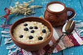 stock photo of oats  - Oatmeal in a clay bowl milk mug homespun mat stalks of oats on a blue wooden background - JPG