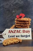 stock photo of biscuits  - Australian Anzac biscuits with Anzac DAy Lest We Forget message on dark wood and slate background - JPG