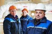 foto of pressure vessel  - three repairman engineer of fire engineering system or heating system open the valve equipment in a boiler house - JPG