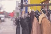foto of thrift store  - A bunch of winter jackets hanging on a rail outside - JPG