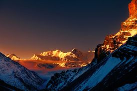 stock photo of cloudy  - beautiful cloudy sunrise in the mountains with snow ridge - JPG