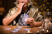 stock photo of fortune-teller  - Close up of aged fortune teller reading tarot card meaning - JPG