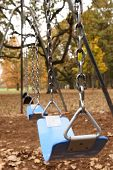 picture of swingset  - a stock image of a lonely swing set in a park during autumn - JPG
