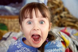 picture of screaming  - Shocked screaming little girl with opened mouth in her bedroom - JPG
