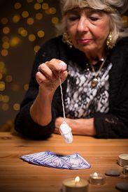 foto of pendulum  - Photo of female seer with magic pendulum and tarot cards - JPG