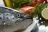 stock photo of salmon steak  - salmon head close up with fresh meat and vegetables in background - JPG