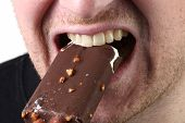 taking a bite of chocolate coated icecream