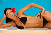 stock photo of woman bikini  - Beautiful young Sexy woman laying in bikini during sunbath next to swimming pool - JPG