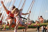 pic of amusement park rides  - A mother and daughter having fun on amusement park swings.